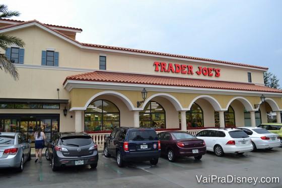 Foto do exterior do supermercado Trader Joe's em Orlando, pintado de bege claro, com o nome do local em letras vermelhas e diversos carros estacionados na frente.