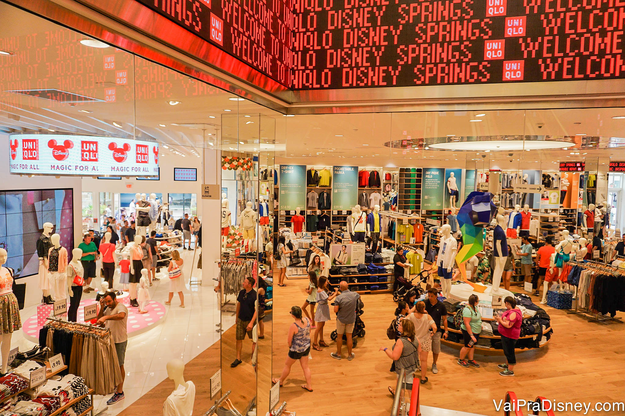 Imagem da loja UNIQLO de Disney Springs. A loja é espaçosa, há roupas em exposição em uma vitrine e muitos visitantes.