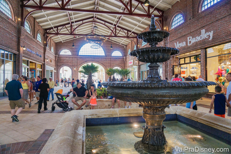Foto das lojas em Disney Springs, em uma área coberta, com a fonte em primeiro plano.