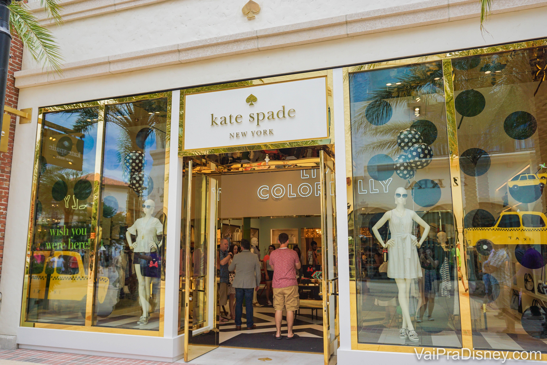 A foto mostra a vitrine da loja Kate Spade em Disney Springs, com manequins exibindo bolsas e óculos escuros.
