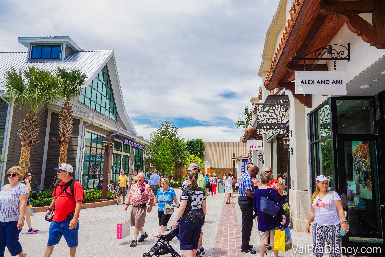 Foto de algumas lojas em Disney Springs, com visitantes passando entre elas.