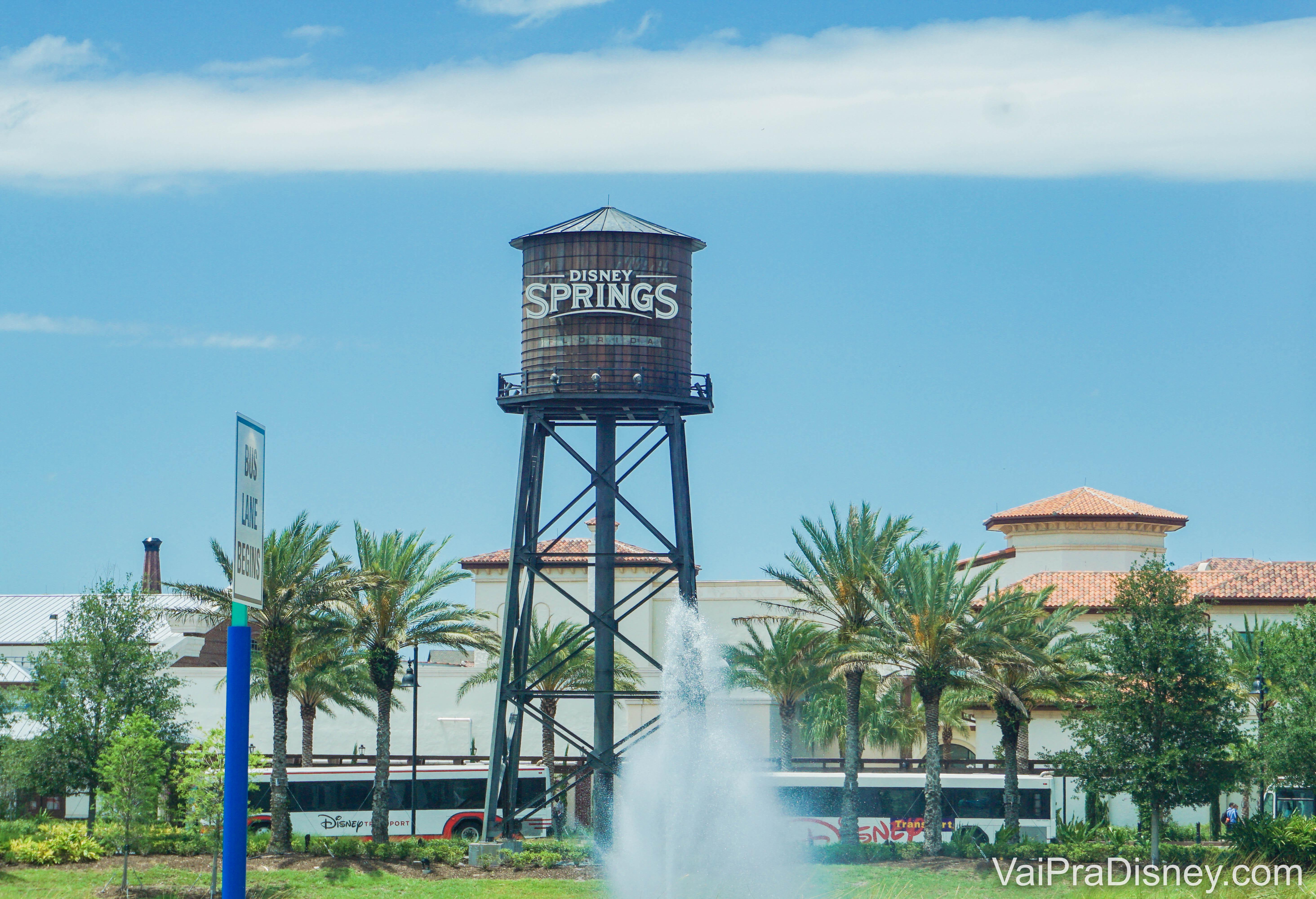Imagem da caixa d'água com o logo de Disney Springs, com árvores ao redor e o céu azul atrás.