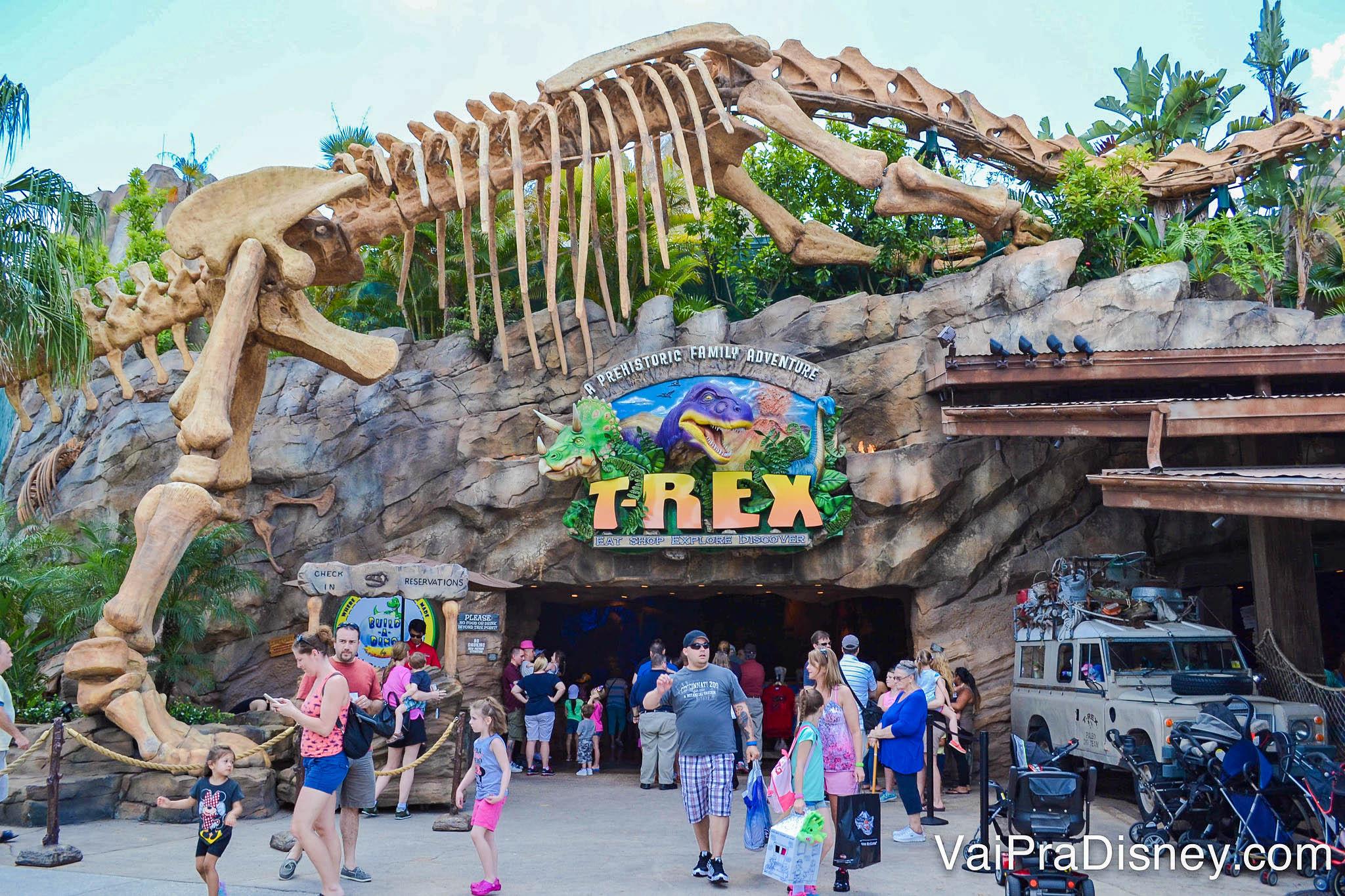 Foto da entrada do restaurante T-Rex em Disney Springs, que tem um esqueleto de dinossauro gigante e é todo em pedra, como uma caverna.