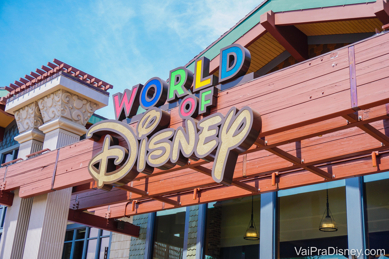 """Foto da placa da loja World of Disney, que fica em Disney Springs e é a maior loja Disney do mundo. A placa tem letras coloridas e a palavra """"Disney"""" em uma cor só, bege."""