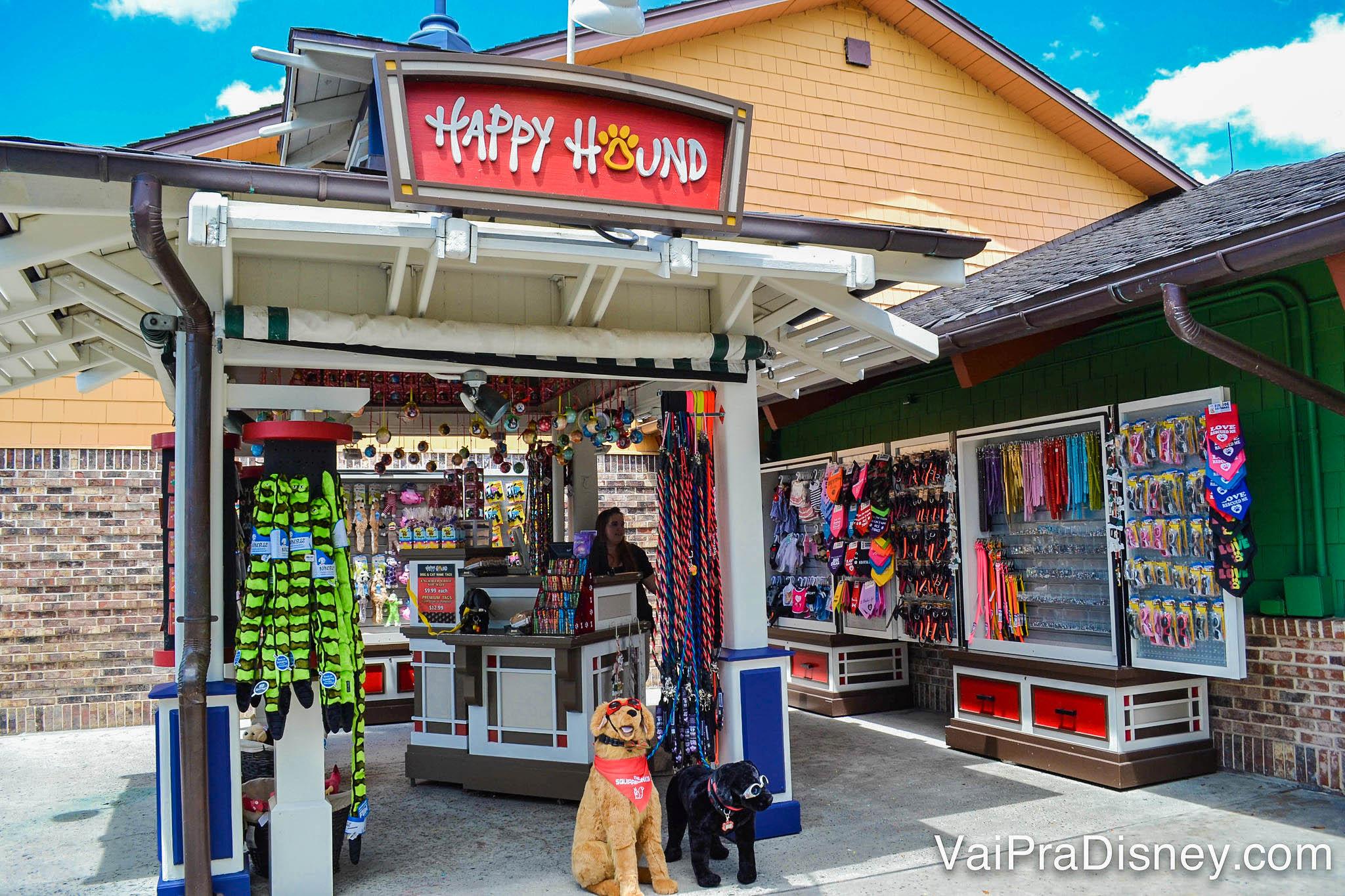 Foto do quiosque Happy Hound, que vende produtos para cachorros. Há um cachorro de pelúcia em frente, com bandana e óculos escuros.