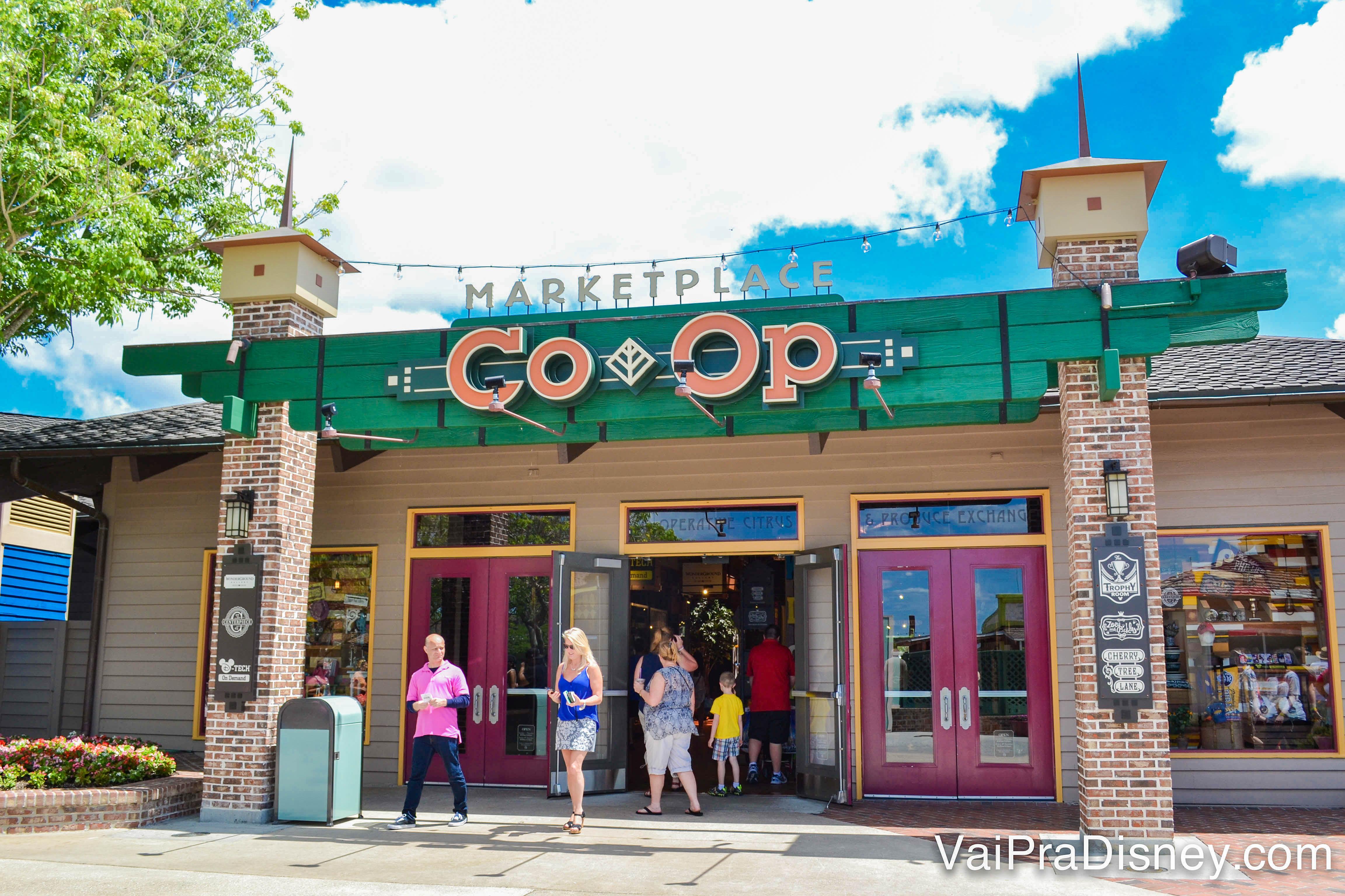 Foto da entrada do Marketplace Co-op de Disney Springs. A fachada é verde e as letras estão em laranja.