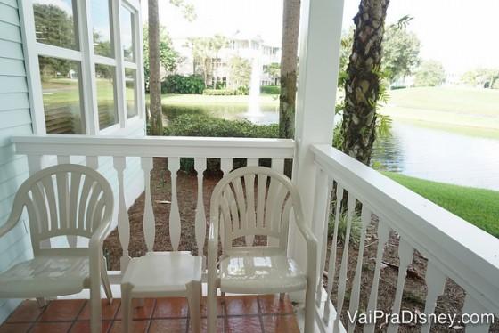 A varanda do quarto, com vista para as árvores e o lago e algumas cadeiras brancas
