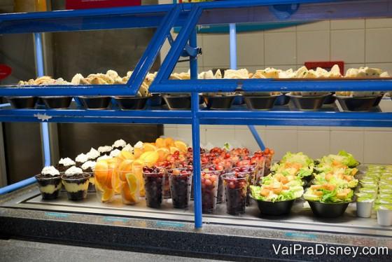 Foto das opções de comida, com as saladas, frutas e sobremesas