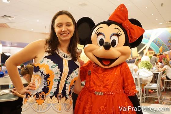 Foto da Renata com a Minnie em um vestido vermelho de gala e laço combinando