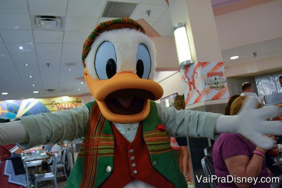 Foto do Pato Donald abrindo os braços para a câmera em um abraço, vestido com roupa verde e vermelha pro Natal