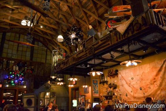 Foto mais ampla do bar, mostrando os muitos itens de decoração como mapas e partes de avião