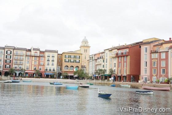 Foto do Portofino Bay durante o dia, com o lago, barcos passando e as lojas e restaurantes mais ao fundo