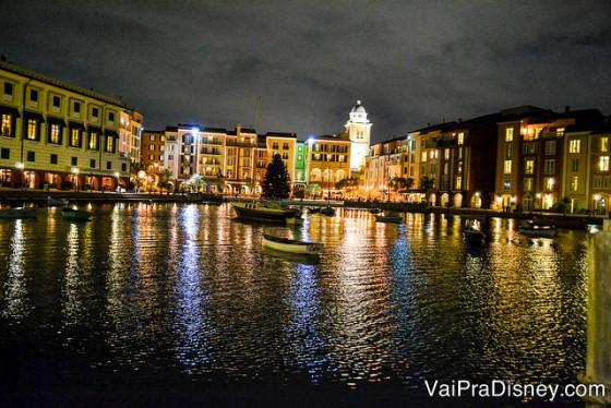 Foto do Portofino Bay iluminado durante a noite, com o lago, um barco passando e as lojas e restaurantes mais ao fundo