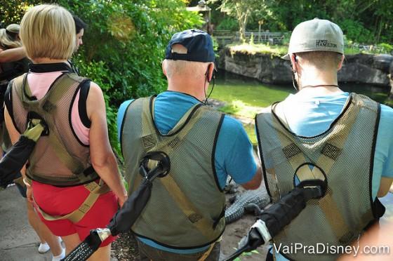 Três visitantes com aparelhos de segurança presos às costas na hora da travessia sobre os crocodilos