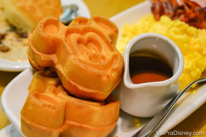 Waffles do Mickey ao lado de uma leiteira com calda de chocolate