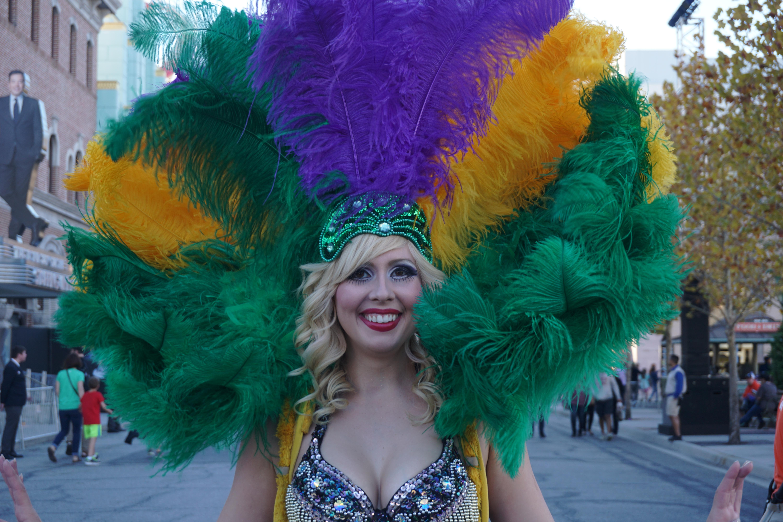 Foto de uma dançarina caracterizada para o Mardi Gras, com plumas coloridas na cabeça.