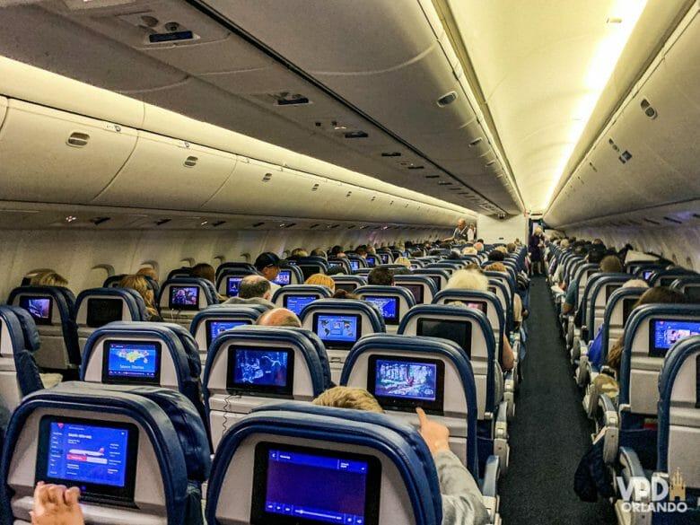 Foto do corredor no interior de um avião. É possível ver a parte de trás de diversas fileiras de poltronas, com as telas acopladas atrás.