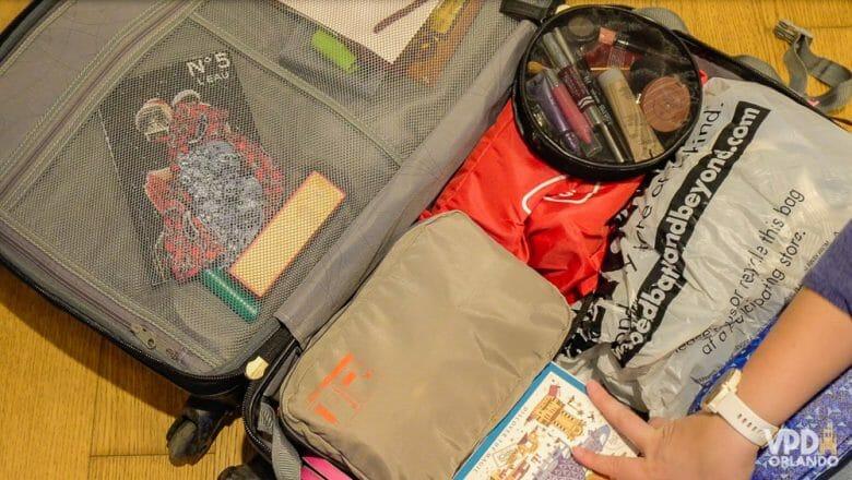 Foto do interior de uma mala de viagem, com diversos saquinhos para guardar roupas e uma nécessaire