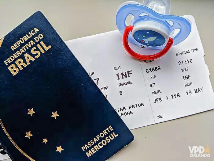 Foto de um passaporte brasileiro com uma passagem de avião embaixo e uma chupeta ao lado.