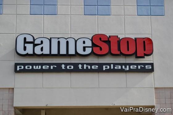 """Game Stop em Orlando. Uma das minhas lojas preferidas na cidade. Foto da entrada da Game Stop em Orlando. A placa tem a palavra """"Game"""" escrita em branco e """"Stop"""" escrita em vermelho."""