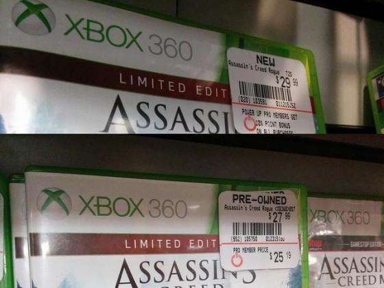 """Em um lançamento, a diferença entre jogos novos e pre-owned podem não ser tão grandes. Foto do mesmo jogo, Assassin's Creed, com etiquetas de preços diferentes, um marcado como """"new"""" e outro """"pre-owned"""""""