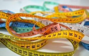 Foto de diversas fitas métricas coloridas, ilustrando o post a respeito de medidas de roupas e calçados nos Estados Unidos