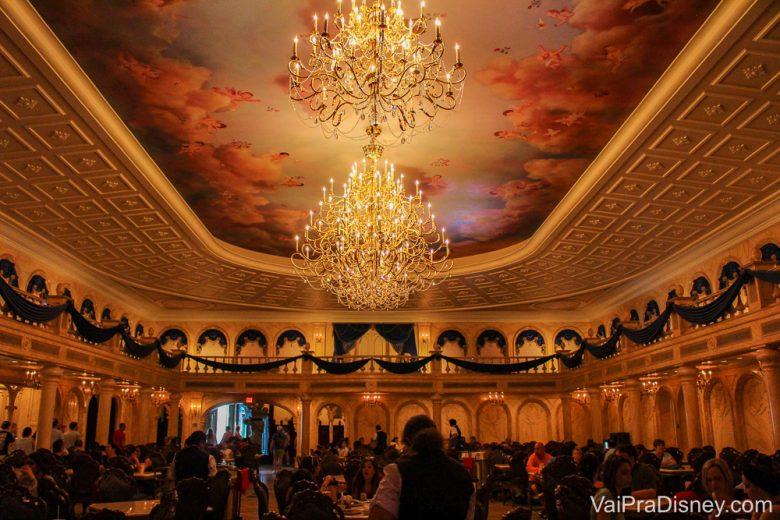 Foto da decoração, do lustre e das mesas no Be our Guest, o restaurante que fica no castelo da Fera no Magic Kingdom