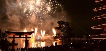 Foto do show de fogos Illuminations, no Epcot, em que os fogos são lançados de dentro do lago. É possível ver o portal do pavilhão do Japão e os fogos explodindo atrás.