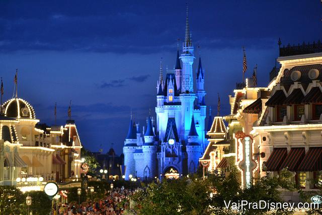 Foto do castelo da Cinderela do Magic Kingdom iluminado em azul, com o céu noturno ao fundo e as luzes da Main Street acesas