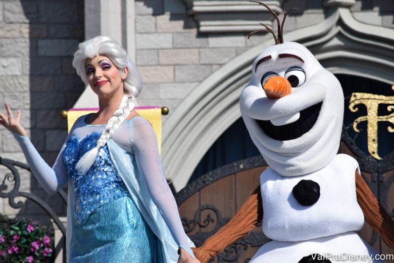 Personagens de Frozen se juntam aos clássicos para o show em frente ao castelo. Foto de Elsa de mãos dadas com Olaf em frente ao castelo da Cinderela no Magic Kingdom