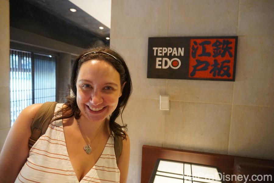 Foto da Renata em frente à placa com ideogramas japoneses do Teppan Edo, restaurante delicioso no Epcot.