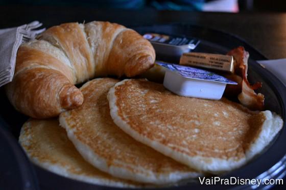 Prato com panquecas e croissant no café da manhã.