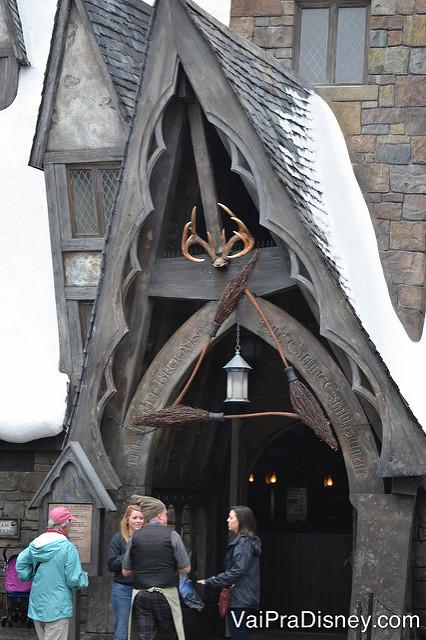 As 3 vassouras formando um triângulo sobre a porta do restaurante, com um chifre de veado mais acima