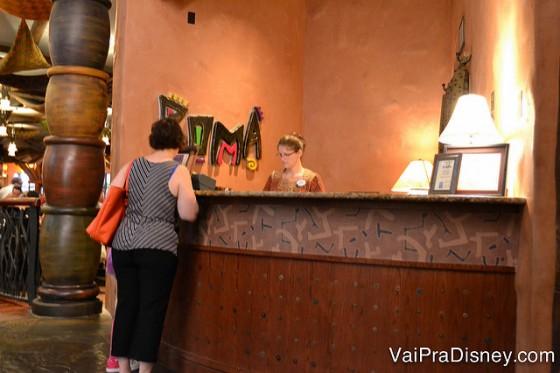 Foto da recepção, com uma visitante em frente ao balcão e a atendente atrás