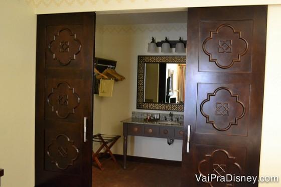 A área do banheiro separada do quarto por portas de madeira
