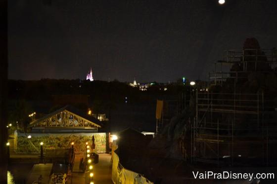 Foto da janela com vista para o parque. É possível ver o castelo da Cinderela iluminado de longe.