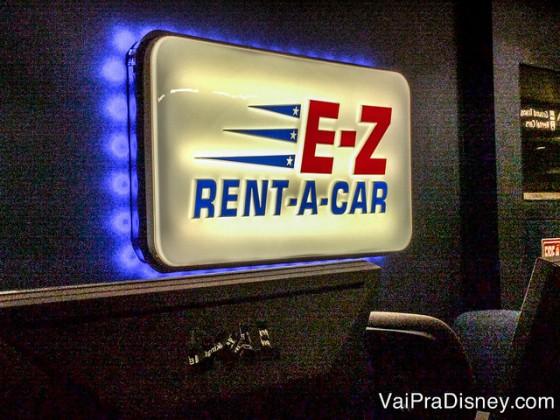 Placa da locadora de carros E-Z Rent-A-Car no aeroporto de Orlando, com fundo branco e letras em vermelho e azul