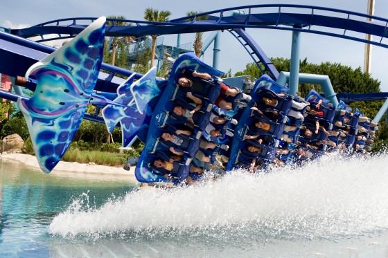 Foto da Manta, no SeaWorld, com os carrinhos da montanha-russa mergulhando na água durante uma das curvas.