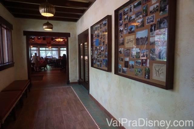 Foto do corredor de acesso ao Nomad Lounge com várias fotos de viajantes expostas em molduras de madeira