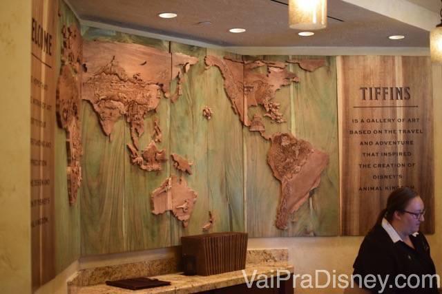 Foto de um mapa mundi de madeira na decoração, na parede do Tiffins