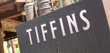Placa do Tiffins, cinza e com letras brancas, no Animal Kingdom