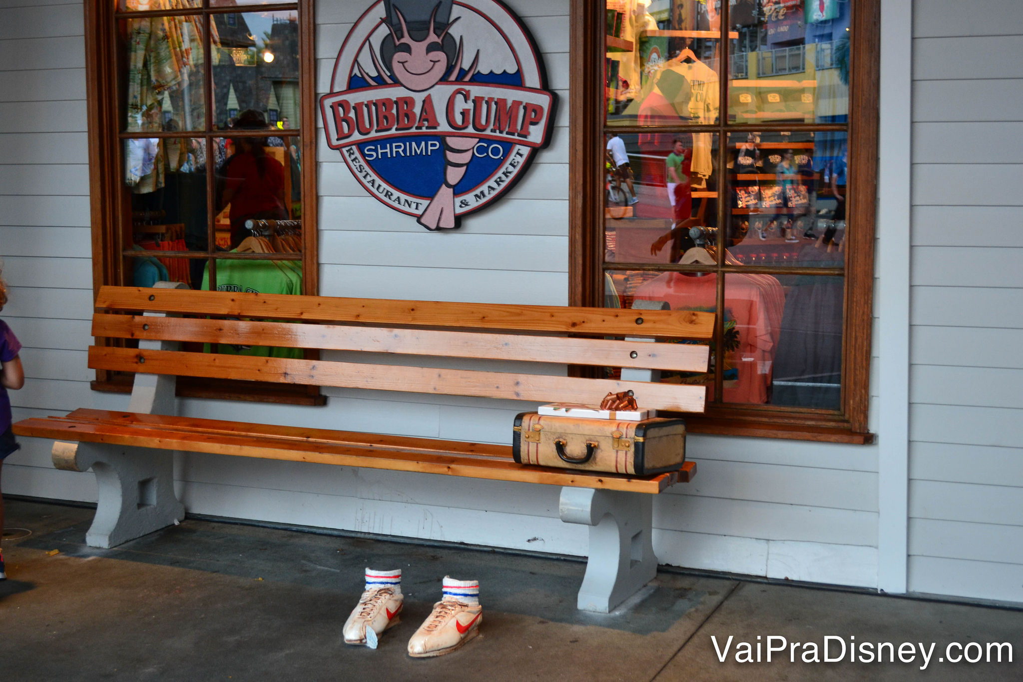 Foto do banco no exterior do Bubba Gump, com os tênis e a maleta de Forrest do filme Forrest Gump