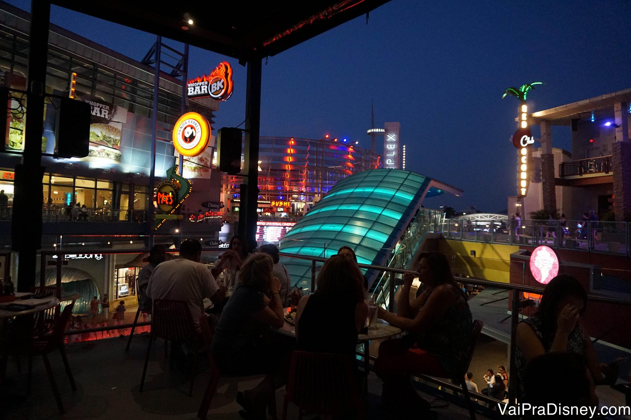 Foto da sacada de um restaurante à noite, com vista para o CityWalk iluminado