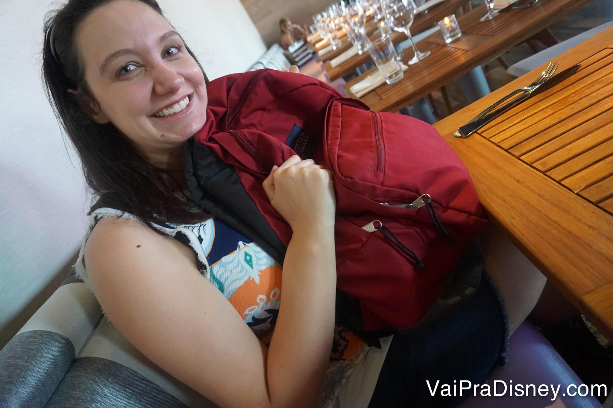 Foto da Renata sentada à mesa do restaurante abraçada na mochila