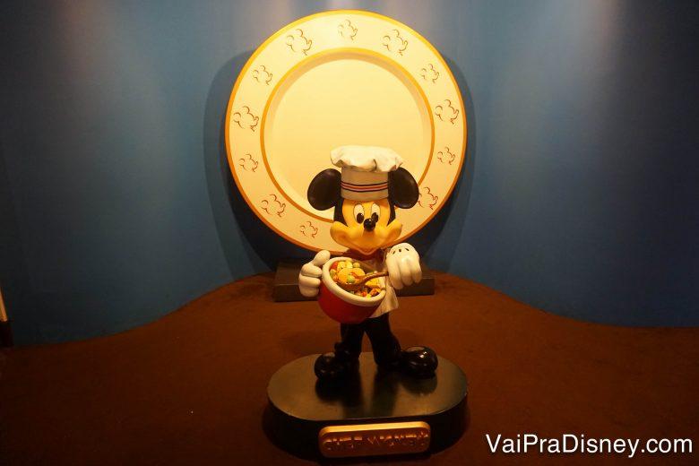 Foto de uma estátua do Mickey vestido de Chef, mexendo a comida em uma panela.
