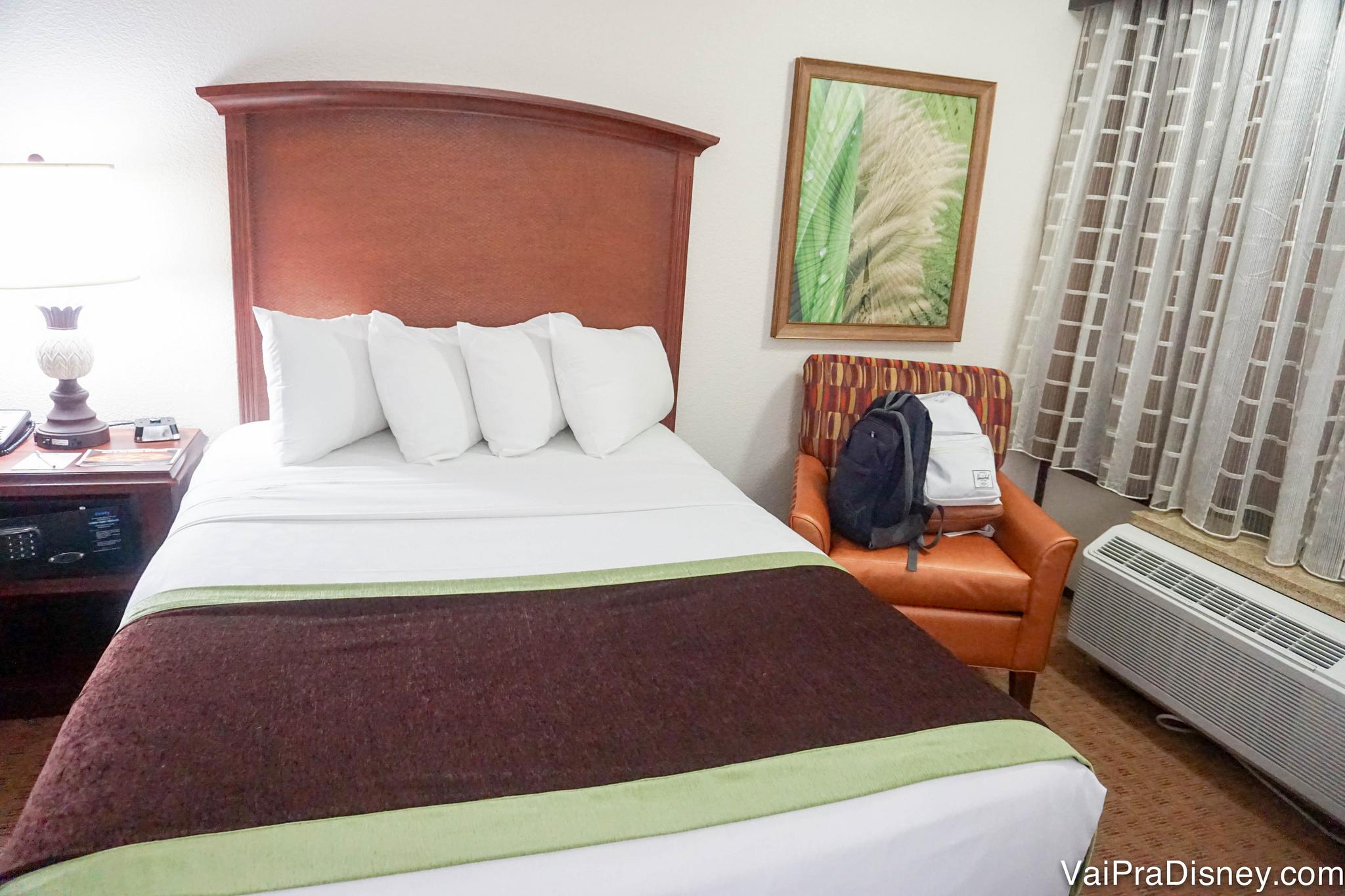 Uma das camas do quarto padrão do Rosen Inn Lake Buena Vista, com uma poltrona e ar condicionado ao lado.
