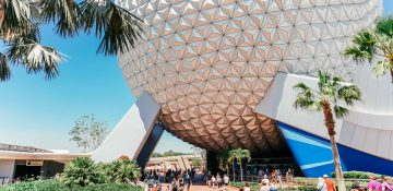 """Foto da """"bola"""" que é símbolo do Epcot, onde fica a atração Spaceship Earth, com o céu azul ao fundo e alguns visitantes passando ao redor."""