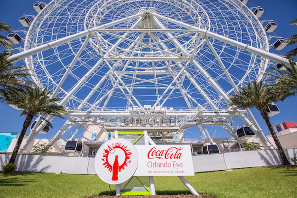 """Antigamente era Coca-Cola Orlando Eye, agora é The Wheel! Foto da roda-gigante conhecida como The Wheel, em Orlando, com o céu azul ao fundo e a antiga placa com o nome """"Coca-Cola Orlando Eye"""""""