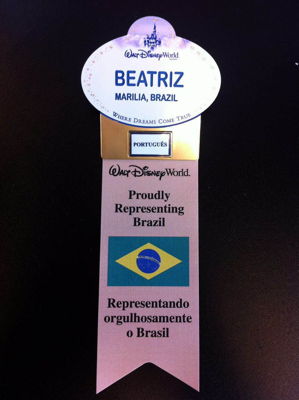 """O dia que eu descobri que a Bia nasceu em Marilia e não Assis!  Foto do crachá da Bia quando ela trabalhou na Disney, indicando que ela nasceu em Marília, fala português e embaixo, uma bandeira do Brasil e o texto """"proudly representing Brazil"""" com tradução mais abaixo"""