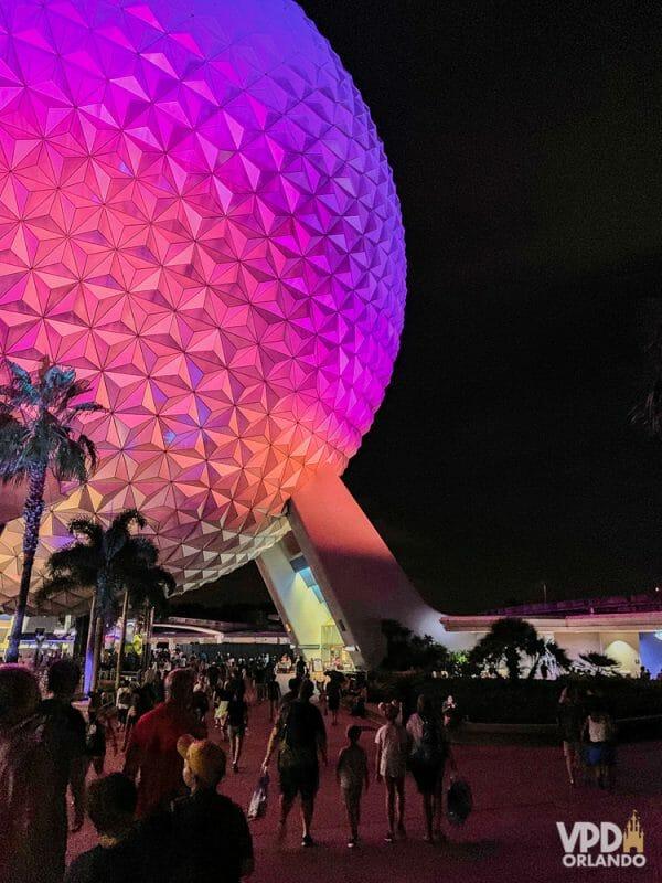 """A """"bola do Epcot"""" também merece uma foto de noite! Foto da """"bola"""" iluminada à noite, em tons de rosa e roxo"""